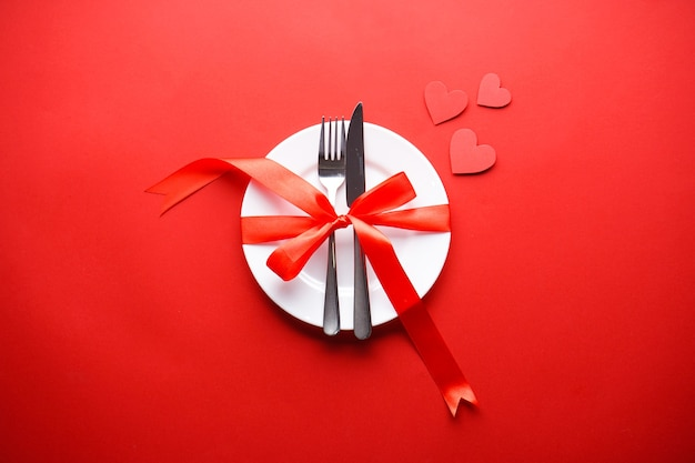 Valentine's day. love concept. mothers day. hearts with cutlery on a white plate with a red ribbon on a red background, flat lay.