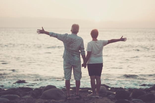 노인들과 함께하는 발렌타인 데이 사랑의 커플 개념은 그들 앞에서 바다와 일몰과 함께 팔을 벌립니다-영원히 함께 관계와 결혼-절대 로맨틱하고 로맨스 느낌