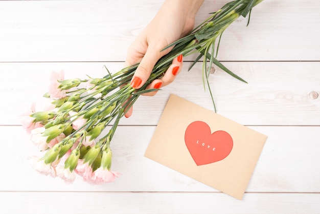 木製の背景にバレンタインデーのラブレター。茶色の封筒、ピンクのメモ、テーブルの上のギフトボックス。赤いマニキュアの女性の手