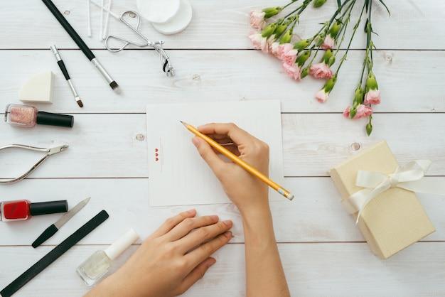 木製の背景にバレンタインデーのラブレター。赤いベルベットのハート型のクッキー、キャンディー、コーヒー。赤いマニキュアの女性の手