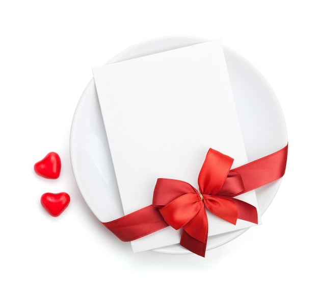 Valentine's day love letter over plate with red bow. isolated on white background
