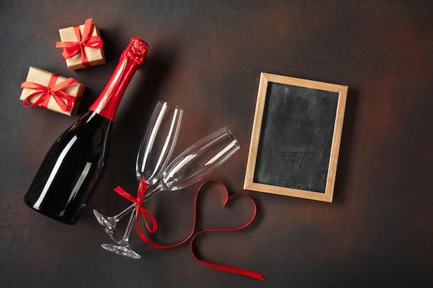 Доска объявлений дня святого валентина с бокалами шампанского и лентой в форме сердца.