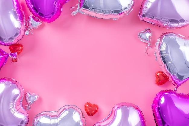 Минималистичная концепция дизайна на день святого валентина - красивый воздушный шар из фольги в форме настоящего сердца, изолированный на бледно-розовом фоне