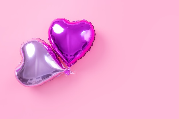 Valentine's day minimal design concept - beautiful real heart shape foil balloon isolated on pale pink background