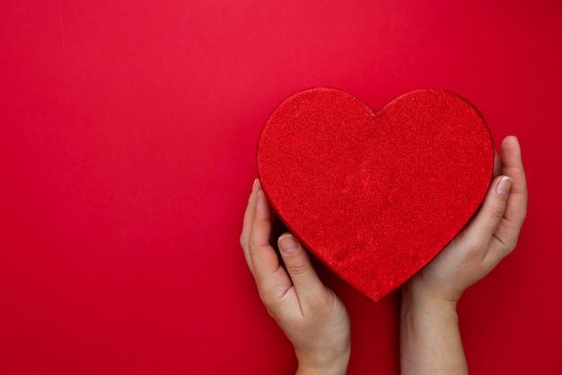 День святого валентина макет. женские руки держа коробку сердца на красной предпосылке с космосом экземпляра. абстрактная красная подарочная коробка.