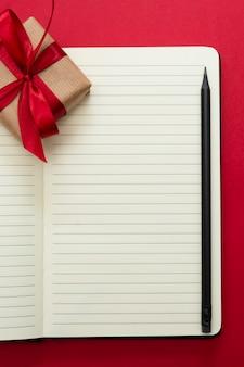 バレンタインデーのモックアップ。赤い背景の上のギフトボクセでノートブックを開く、テキスト用のスペースをコピーします。