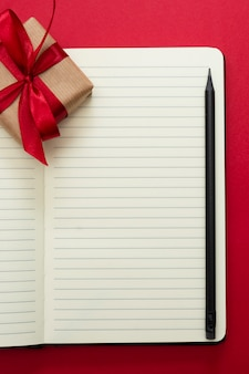 Valentine's day mock up. open notebook with gift boxe, on red background, copy space for text.