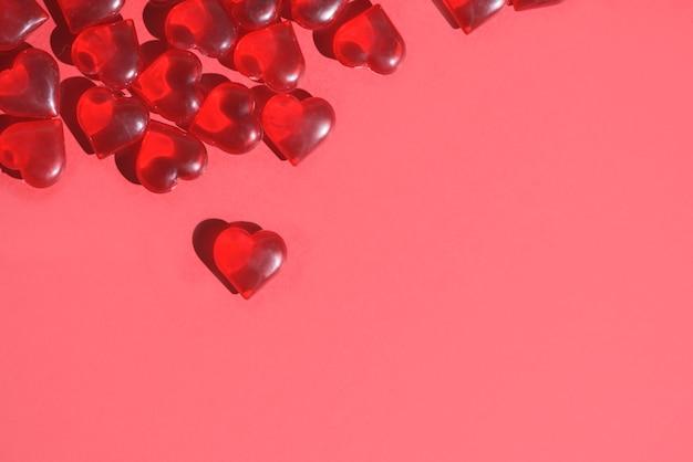 テキストの場所のための、赤い背景に赤いハートのバレンタインデーのモックアップグリーティングカード。お祝いの結婚式の背景、青い焦点。