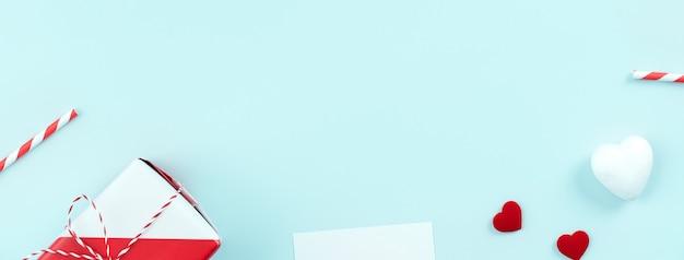 バレンタインデー、プロモーションのための母の日アートデザインコンセプト-パステル水色の背景、フラットレイ、上面図で分離された赤、白のラップされたギフトボックス。