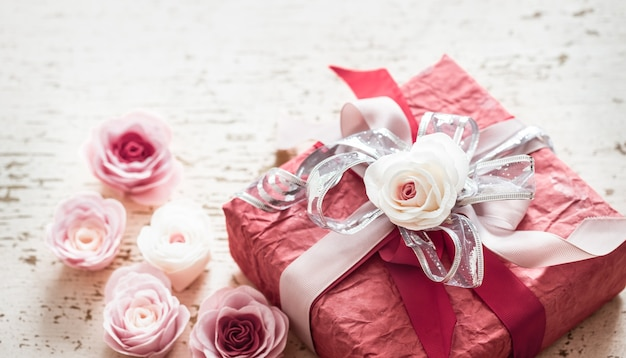Valentine's day and mother's day concept, red gift box with bow and roses on light wooden background