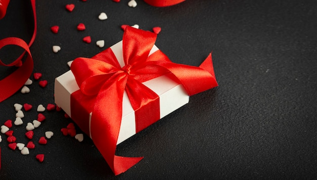 Valentine's day, mother's day, march 8th. gift box with a red bow and red ribbon, red hearts. copy space.