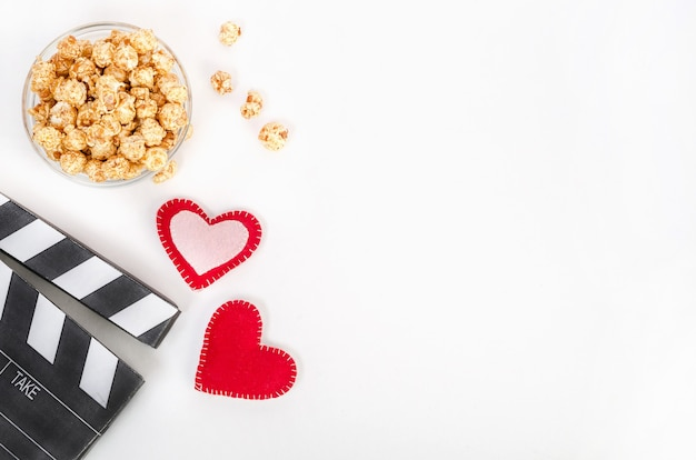 Valentine's day movie concept. clapperboard with hearts and caramel popcorn with copy space on a white background.