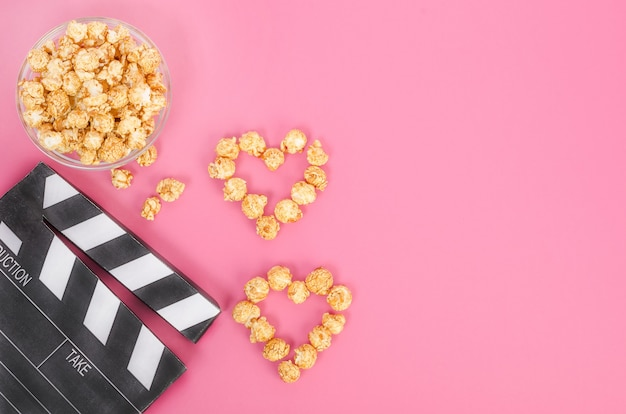 Valentine's day movie concept. movie clapperboard with caramel popcorn hearts with copy space on a pink background.