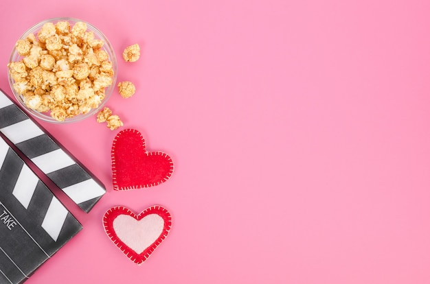 バレンタインデーの映画のコンセプト。ピンクの背景にコピースペースとハートとキャラメルポップコーンと映画のカチンコ。