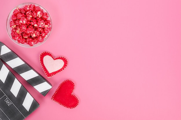 Valentine's day movie concept. movie clapperboard with hearts and red caramel popcorn with copy space on pink background.