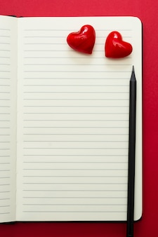 Valentine's day. open notebook with red hearts and a pencil, on red background, copy space for text.