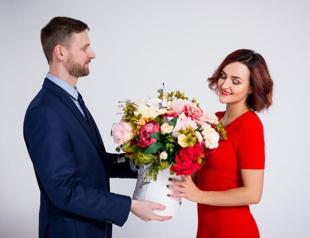 День святого валентина или концепция сюрприза на день рождения - красивый мужчина удивляет свою девушку цветами на белом фоне