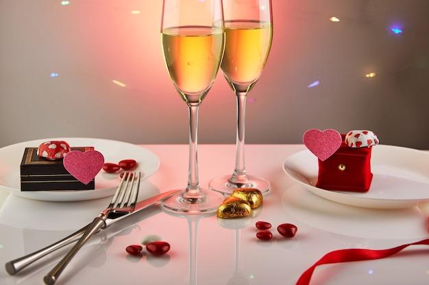 День святого валентина или романтический праздничный ужин с конфетными сердечками, бокалами шампанского и элегантным