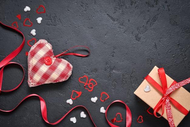 발렌타인 데이 또는 낭만적인 저녁 식사. 패브릭 장난감으로 만든 마음으로 빈 검은 접시. 텍스트를 위한 장소가 있는 어두운 배경 테이블에 있는 축제 서버. 평면도.