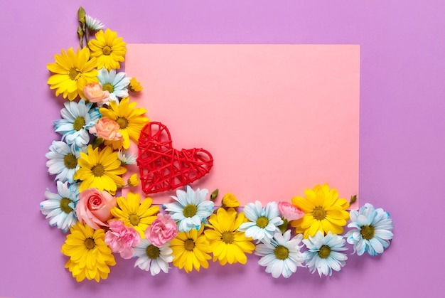 ピンクの背景に花と赤いハートのバレンタインデーまたは結婚式のロマンチックなコンセプト。上面図、コピースペース。
