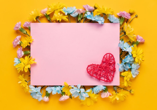 花と黄色の背景に赤いハートのバレンタインデーまたは結婚式のロマンチックなコンセプト。上面図、コピースペース。