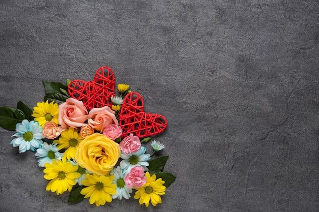 花と灰色の背景に赤いハートとバレンタインデーまたは結婚式のロマンチックなコンセプト。上面図、コピースペース。