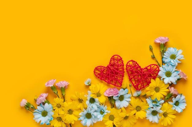 バレンタインデーまたは黄色の背景に花と赤いハートの結婚式のロマンチックなコンセプト。上面図、コピースペース。