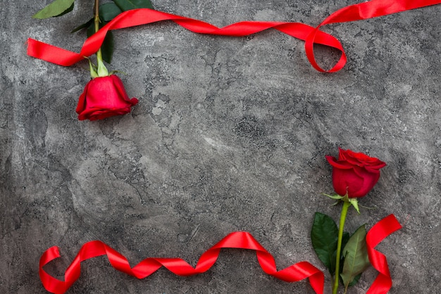 Valentine's day or other love holiday. on a gray background, red trojans are decorated with red ribbon, top view