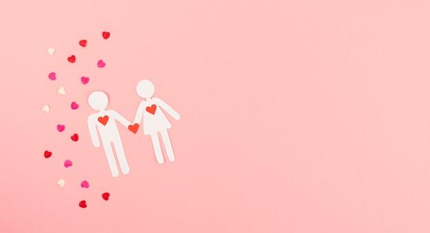 День святого валентина. пара вырезать из бумаги на розовом фоне с украшением сердца. копировать пространство