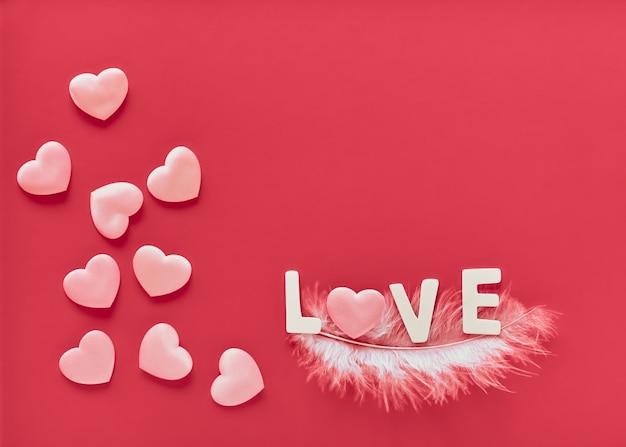 ピンクのハートと白い羽に白い木製の文字が並ぶ愛という言葉とバレンタインデーのピンクの背景。 3月8日母の日グリーティングカード