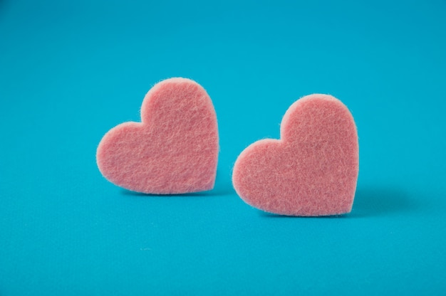 Valentine's day, pink felt hearts on blue background