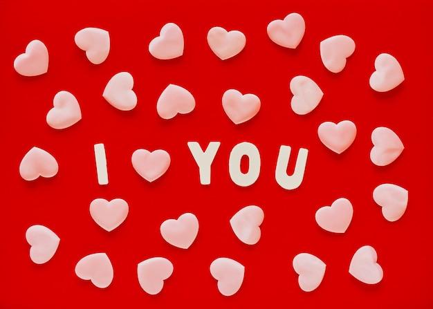 ピンクのハートとフレーズiloveyouとバレンタインデーの赤い背景に白い木製の文字が並んでいます。 3月8日母の日グリーティングカード
