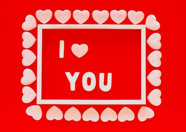 白いフレーム、単語iあなたとピンクのハートとバレンタインデーの赤い背景。母の日、3月8日グリーティングカード、2月14日。