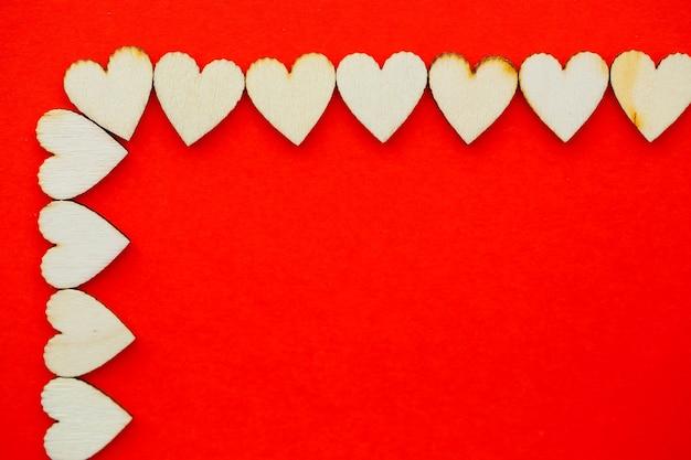 木製の心と愛という言葉でバレンタインデーの赤い背景。碑文、広告のための場所