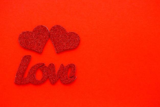 День святого валентина красный фон с деревянными сердцами и словом любовь. место для надписей, рекламы
