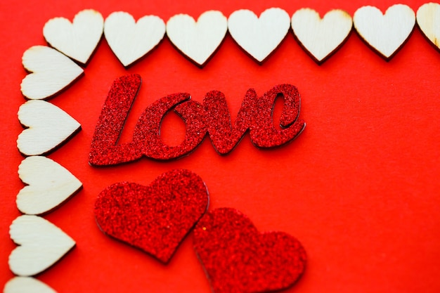 Valentine's day red background with wooden hearts and the word love. place for inscriptions, advertising