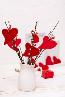 Valentine's day. red felt hearts on willow branches in a white jug on the table, gift and empty foto frame  .