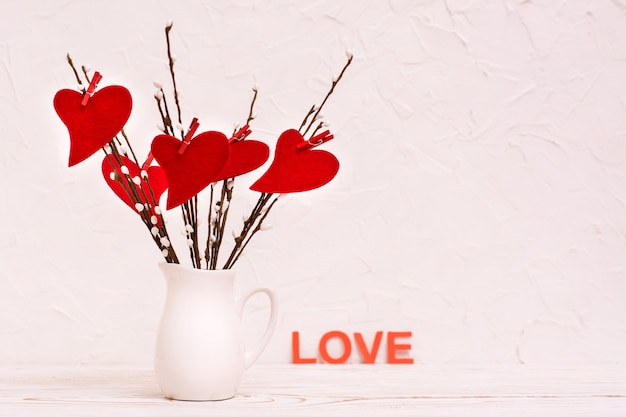 Valentine's day. red felt hearts on willow branches in a white jug on the table and the word