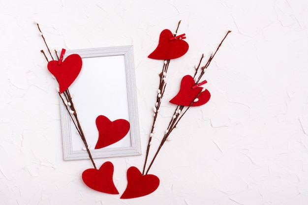 Valentine's day. red hearts made of felt on willow branches on a blank photo frame