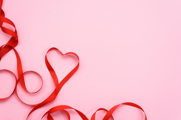 ピンクの背景にハートの形をしたバレンタインデーの赤いリボンの曲線。結婚式やグリーティングカード、モックアップ、コピースペースのお祝いの背景。