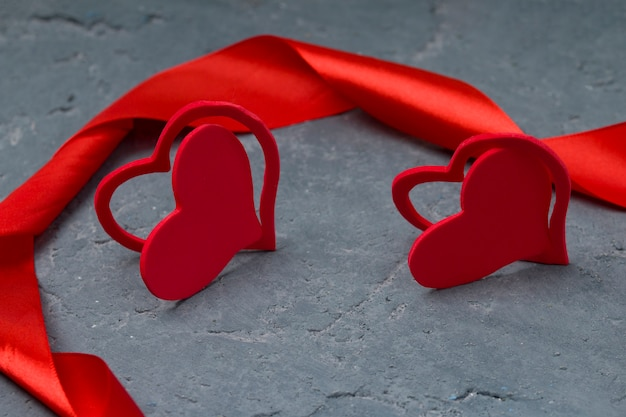 Valentine's day. red ribbon and red hearts. gray concrete background