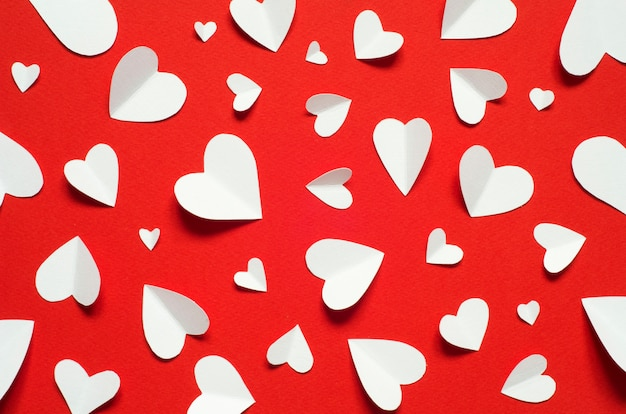 Valentine's day romantic background. white paper hearts at red backdrop, top view.