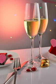 Valentine's day or romantic birthday dinner with candy hearts, glasses of champagne and elegant table setting with reflection and lights in the table.