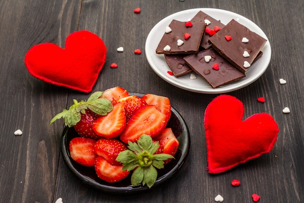 Valentine's day romantic concept. chocolate, fresh ripe strawberry, red felt hearts. sweet dessert for lovers.