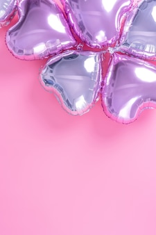 Романтическая концепция дизайна на день святого валентина - воздушный шар из фольги в форме красивого сердца на бледно-розовом фоне