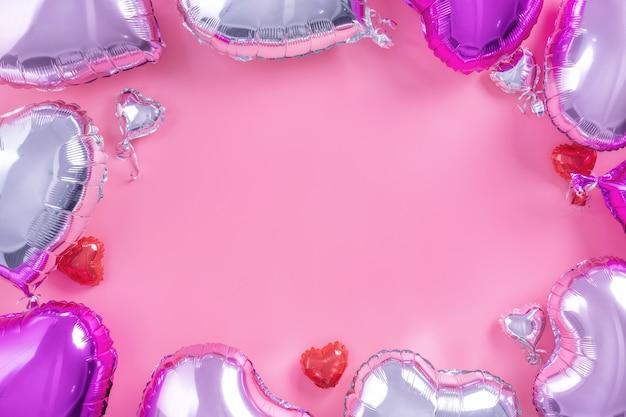 발렌타인 데이 낭만적인 디자인 개념 - 옅은 분홍색 배경, 위쪽 전망, 평평한 평지, 사진 위의 머리 위에 격리된 아름다운 실제 하트 모양의 호일 풍선.