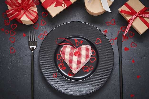 Valentine's day or romantic dinner. empty black plate with heart made of fabric toys. festive server
