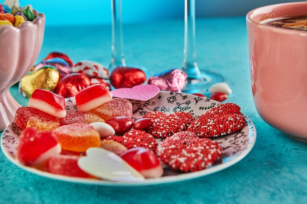 Valentine's day or romantic dinner with candy hearts, a cup of hot coffee and elegant table setting on a light blue table.