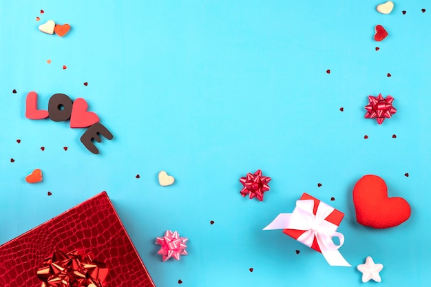 Valentine's day romantic party concept. gift boxes, heart shape, sweets on blue background. top view, flat lay, copy space