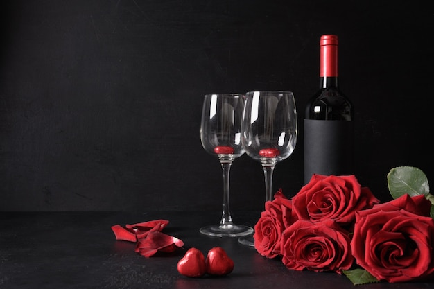 Valentine's day romantic set of red wine and bouquet of red roses, hearts sweets on black. greeting card with copy space. romantic dating. proposal.